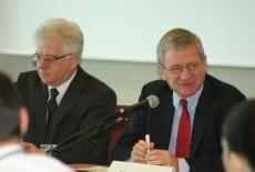 Bogusław Wind mówi do mikrofonu obok niego siedzi Jacek Czaputowicz