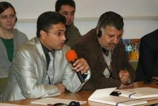 Uczestnicy szkolenia siedzą przy ławkach, jeden z uczestników mówi do mikrofonu