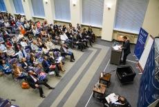 Widok z góry na Aule , Ambasador przemawia przy mównicy do zgromadzonych gości na auli