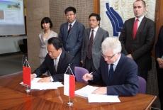 przedstawiciel delegacji Chin i Dyrektor KSAP siedza przy stole i podpisują dokumenty