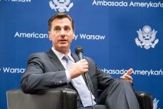 Ambasador USA siedzi w fotelu i mówi do mikrofonu