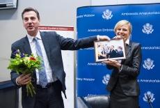 Ambasador USA trzyma w jednym ręku kwiaty a w drugim zdjęcie pamiątkowe, obok stoi Pani