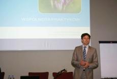 Dr Marcin Sakowicz przemawia w tle prezentacja