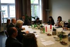 Przedstawiciele delegacji siedzą przy stole i rozmawiaja z przedstawicielami KSAP