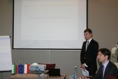 Prowadzący spotkanie stoi przy wyświetlanej prezentacji