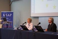 Pani Ewa Sosnowiec siedzi i mówi do mikrofonu obok siedzi Dyrektor KSAP