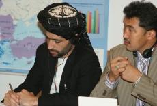 Uczestnicy spotkania notują. jeden z uczestników ma na głowie turban