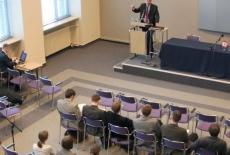 Widok z góry na siedzacych na Auli gości, Daniel Castello toi przy mównicy i przemawia