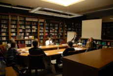 Uczestnicy spotkania siedzą przy stole w bibliotece KSAP