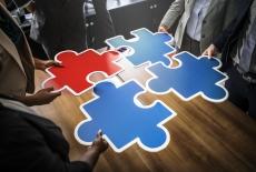 Wokół stołu stoi pięć osób, cztery z nich trzymają duże puzzle, dopasowują je do siebie