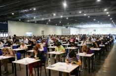 Uczestnicy siedzą w pojedynczych ławkach i piszą test