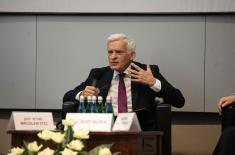 Jerzy Buzek siedzi na fotelu i przemawia, gestykuluje