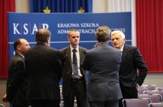 Sześciu mężczyzn stoi na Auli i rozmawia w tym Jerzy Buzek