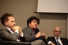 Claudia Torres-Bartyzel siedzi na fotelu, trzyma mikrofon i mówi obok siedzą dwaj mężczyźni