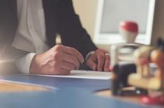 Dłoń trzymająca długopis piszący na białej kartce. Obok na stole stoją pieczątki.