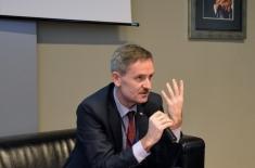 Dariusz Wiśniewski siedzi przy stole prezydialnym w auli KSAP.
