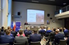 Uczestnicy programu w auli KSAP słuchają wykładu. Na dużym ekranie widać wyświetloną prezentację.