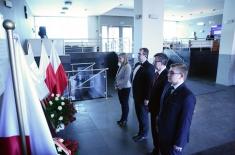 przedstawaiciele KSAP oraz Szef Służby Cywilnej stoją przed tablicą upamiętniającą Patrona KSAP. Widoczne polskie flagi oraz wiązanki.
