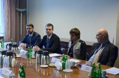 Uczestnicy delegacji podczas spotkania. Siedzą przy dużym stole.