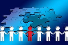 Grafika przedstawiajaca ludziki trzymajace się za ręce. Wszystkie ludziki, oprócz jednego stojącego w środku, są białe. Środkowy jest czerwony. w tle puzzle.