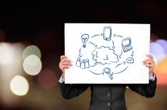 człowiek trzymający przed sobą kartkę z narysowanymi symbolami komputera, żarówki, telefonu, ludzi, lupy, koperty