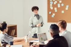 trzy osoby siedzą przy stole, jedna kobieta stoi i mówi do siedzących - prowadzi zajęcia