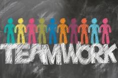 na czarnej tablicy narysowane kolorową kredą ludziki oraz napis: teamwork