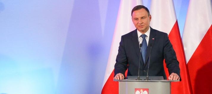 Prezydent Andrzej Duda przemawia przy mównicy. W tle - polskie flagi.