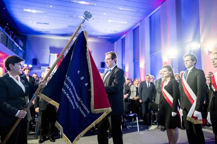 Premier Beata Szydło przekazuje sztandar KSAP Dyrektorowi KSAP. Z prawej strony stoi poczet sztandarowy. W tle uczestnicy uroczystości.