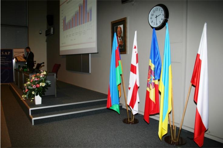 Na pierwszym planie widać flagi, a na drugim osobę stojącą przy mównicy.