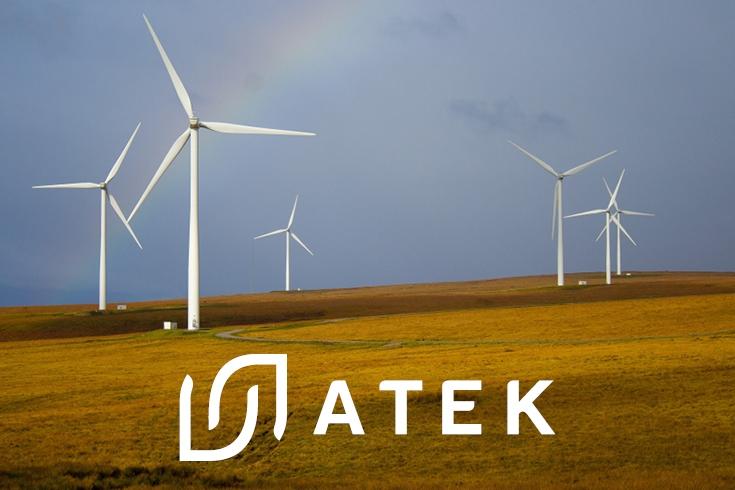 Sześć wiatraków stojących na polu, na tle niebieskiego nieba. Logo Atek na dole zdjęcia.