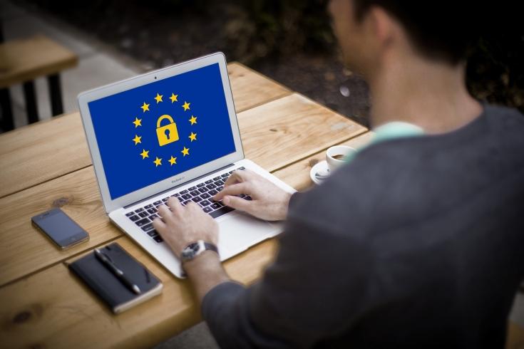 Mężczyzna siedzi przy stole. Przed nim otwarty laptop. Na ekranie na niebieskim tle żółta kłódka a wokół niej żółte gwiazdki Unii Europejskiej.