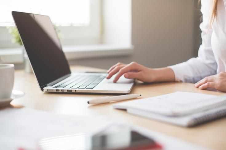 Na biurku stoi laptop. Częściowo widoczna kobieta siedząca przy biurku. Ręka pisze na klawiaturze. Na biurku leżą papiery i długopis.