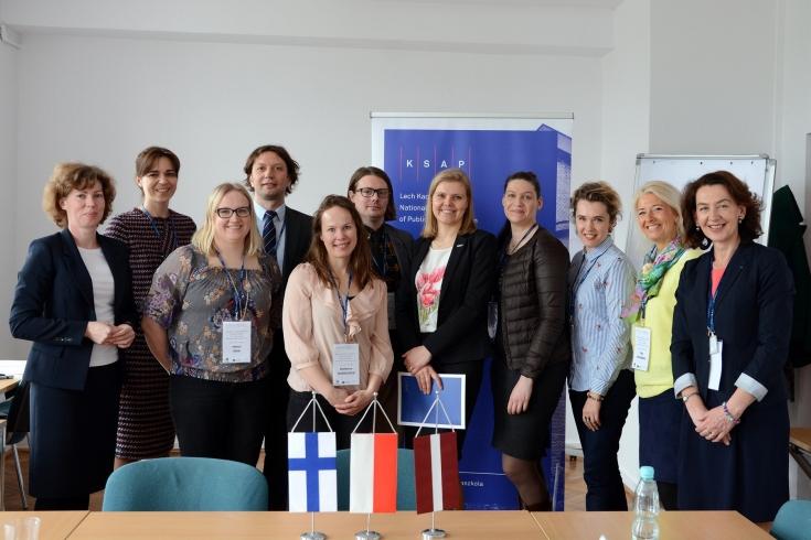 Zdjęcie grupowe wszystkich uczestników spotkania. Na stole przed nimi stoją flagi: polska, fińska i łotewska.