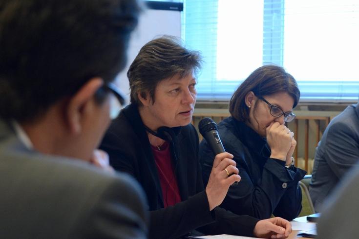 Uczestniczka seminarium siedzi przy stole i mówi do mikrofonu. Obok siedzą pozostali uczestnicy.