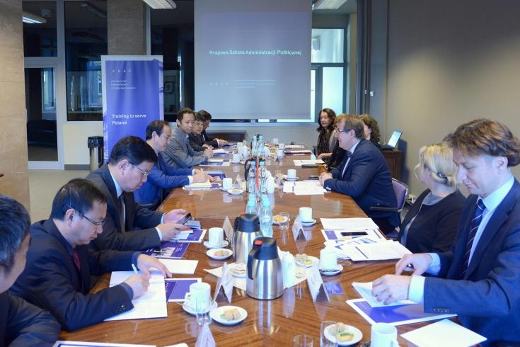 Uczestnicy spotkania siedzą przy dużym stole.