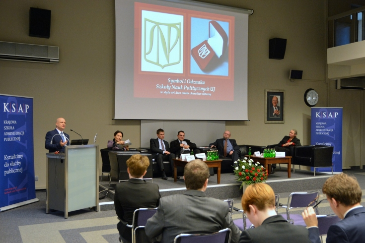 Aula KSAP, Bartosz Włodarski przemawia z mównicy, w prezydium siedzą pozostali paneliści. Na ekranie wyświetolny slajd przedstawiający symbol i odznakę Szkoły Nauk Politycznych UJ.