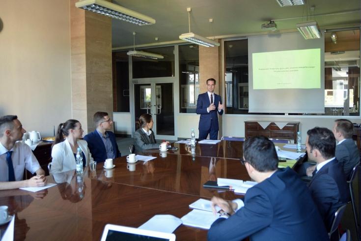 Uczestnicy spotkania siedzą przy dużym prostokątnym stole. Jeden ze słuchachaczy stoi przy ekranie z wyświetloną prezentacją.