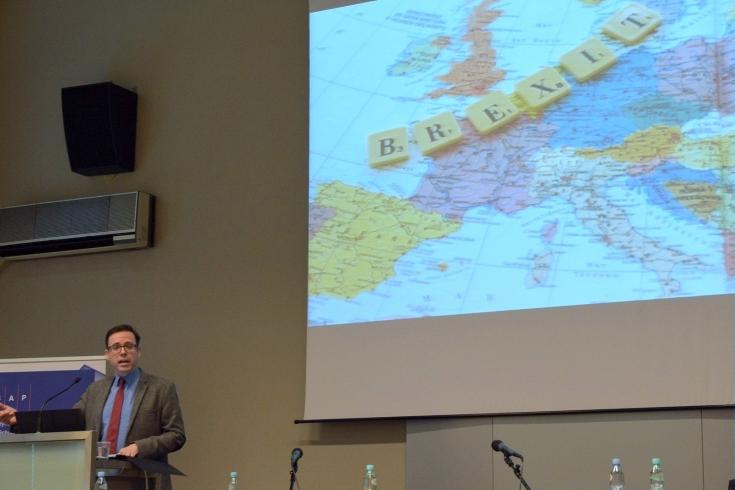 Prowadzący wykład stoi przy mównicy, obok na dużym ekranie wyświetlona mapa Europy z napisem: Brexit.