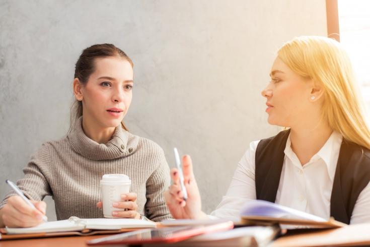 Dwie kobiety siedzą i rozmawiają przy biurku. Na blacie leżą rozłożone notatniki.