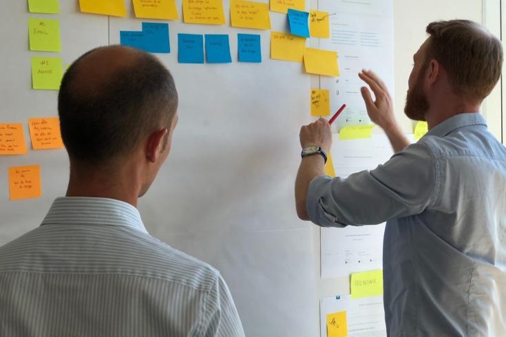 dwóch mężczyzn stoi przy białej tablicy, na której są przyklejone kolorowe karteczki