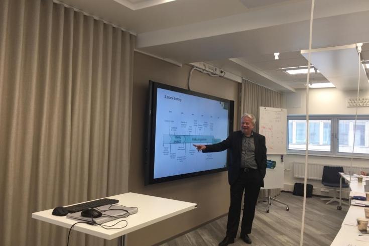 prowadzący zajęcia przy ekranie z wyświetloną prezentacją