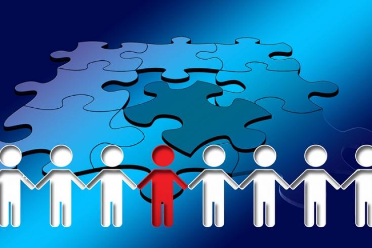 Grafika przedstawiająca ludziki trzymające się za ręce. Wszystkie ludziki, oprócz jednego stojącego w środku, są białe. Środkowy jest czerwony. w tle puzzle.