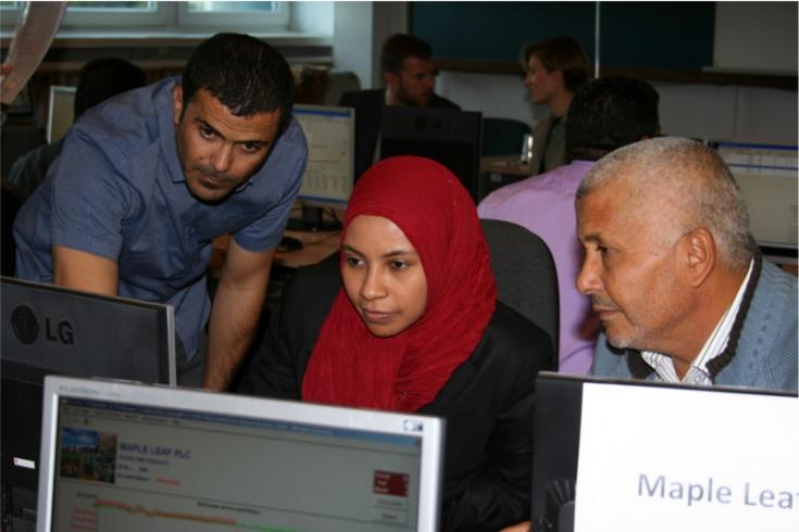 Troje uczestników szkolenia z Libii pracujących przy komputerze