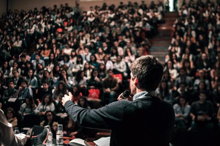 osoba z mikrofonem przed dużą publicznością