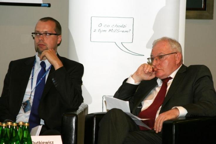 Dwóch uczestników panelu dyskusyjnego siedzi na fotelach