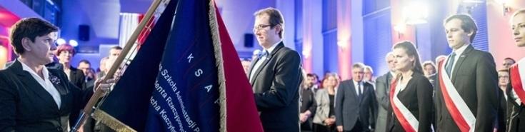 Premier Beata Szydło przekazuje nowy sztandar Szkoły Dyrektorowi KSAP. Za Dyrektorem stoi poczet sztandarowy. W tle zebrani goście.