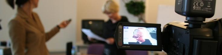 na pierwszym planie widać ekranik kamery na którym widoczna jest kobieta