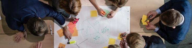 Słuchacze KSAP pracuję przy stole, na którym leży duża biała kartka z narysowanym kołowym wykresem. Przyklejają do niej kolorowe karteczki, na których coś piszą. Zdjęcie zrobione z góry.