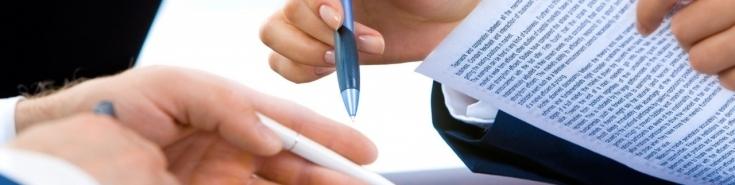 dwie dłonie trzymające długopisy i zadrukowaną tekstem kartkę